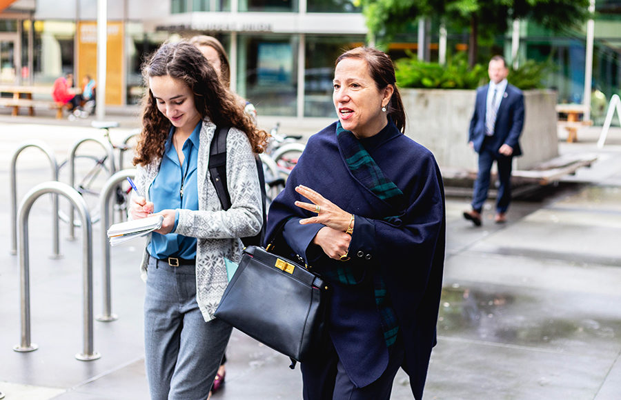 A woman walks and speaks as a student follows and takes notes.