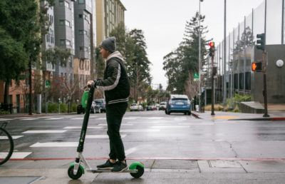 A man riding an electric scooter on a sidewalk during a rainy day.