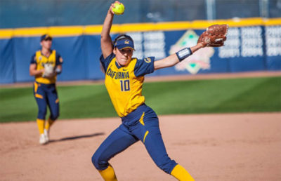 Woman winds arm in preparation to throw softball.
