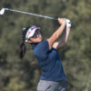 A golf player swings her golf club.