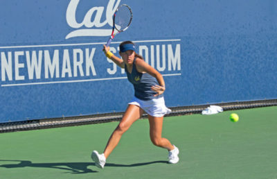 Tennis player prepares to swing at the ball with her racket.