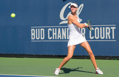 A woman preparing to hit a tennis ball.