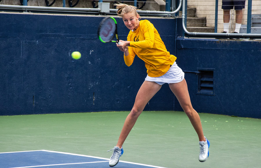 A tennis player strikes the ball with her racket.