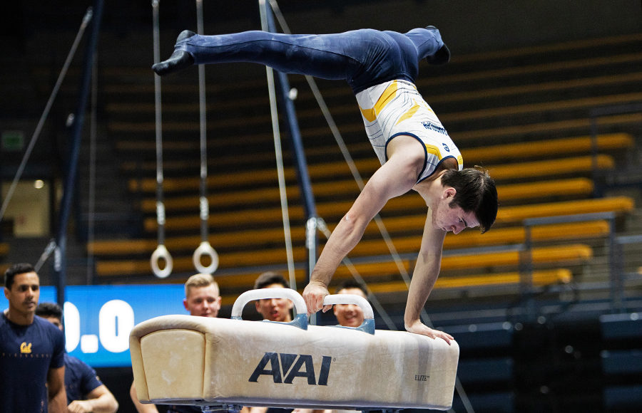 Gymnast stands on his hands atop a beam.