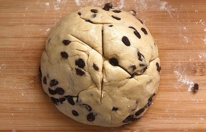 An uncooked ball of dough with raisins.