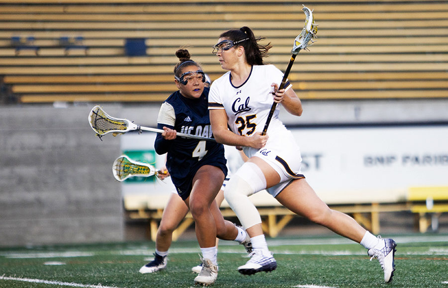 A lacrosse player runs across the field as an opponent player attempts to block them.