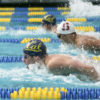 Three swimmers come up for air while in a swimming competition.