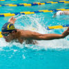 Swimmer comes up for air while swimming through the water.