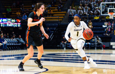 A basketball player bounces the ball and runs down the court as an opponent attempts to block her.