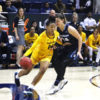 Basketball player bounces ball as opponent tries to block her.
