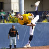 A baseball player kicks his leg back into the air after throwing the ball.