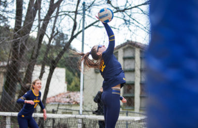 A volleyball player jumps into the air to strike the ball over the net.