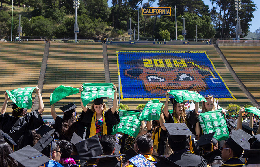 A group of students in caps and gowns hold up green shirts in the middle of their graduation ceremony.