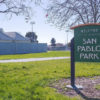 "A sign that reads ""San Pablo Park"" stands in a grassy area."