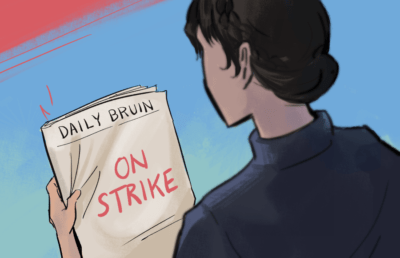 "A person reading the Daily Bruin paper which reads ""On Strike"""
