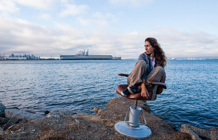 A woman sits on a chair that is sitting on the edge of the ocean.