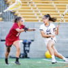 A lacrosse athlete runs with her stick as another player attempts to block her.