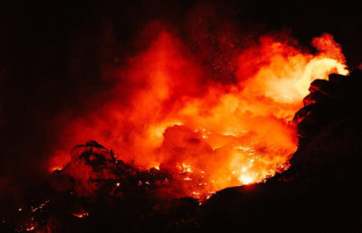 Flames burst into the air above a rocky landscape.