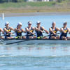 A group of athletes row one boat through the water.