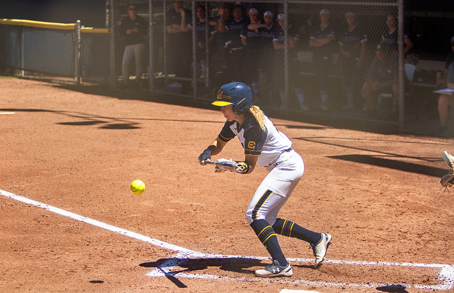 Softball player swings at the ball
