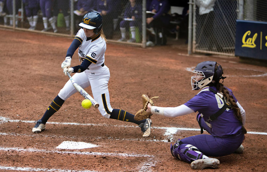A softball player swings at the ball.