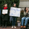 Four women hold signs outside of a building as one speaks into a megaphone.