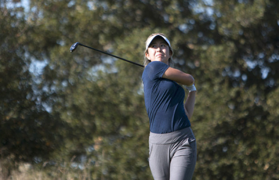 A golf player swings her club.