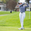 A golf player swings her club at the ball.