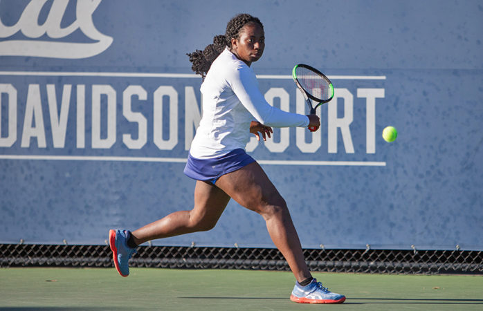 A tennis player swings her racket at the ball.