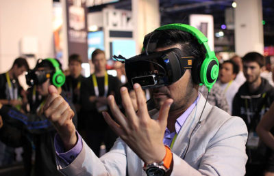 Person in headset and virtual reality googles hold out hands at eye level