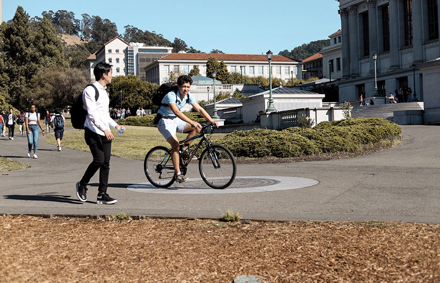 File of a biker and a pedestrian on the UC Berkeley campus.
