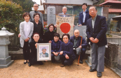 Photo of the family of Haruo Saito holding the flag that belonged to him during WW2 and that was returned to them by the Obon Society