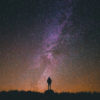 Photo of a person in front of a dark sky full of stars