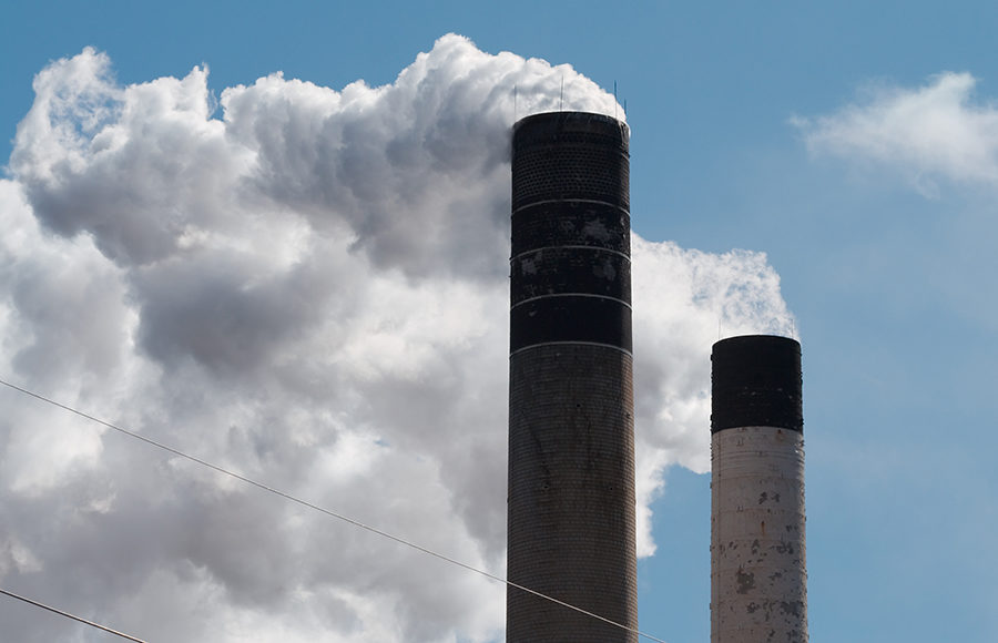 Photo of smokestacks arising out of factory chimneys