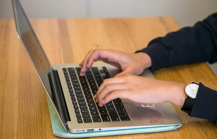 Photo of hands typing on a Macbook computer keyboard