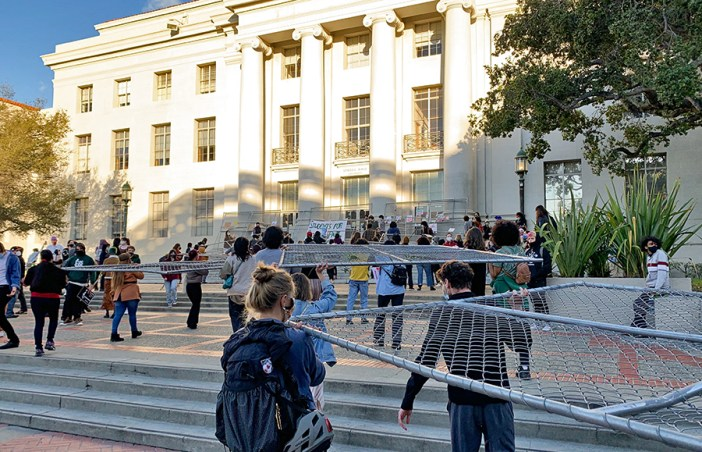 People carrying fences toward the Sproul Hall Steps