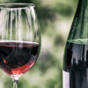 Photo of a wine bottle and wine glass filled with wine