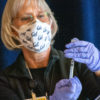 Photo of UC Berkeley employee holding a vial of a COVID-19 vaccine