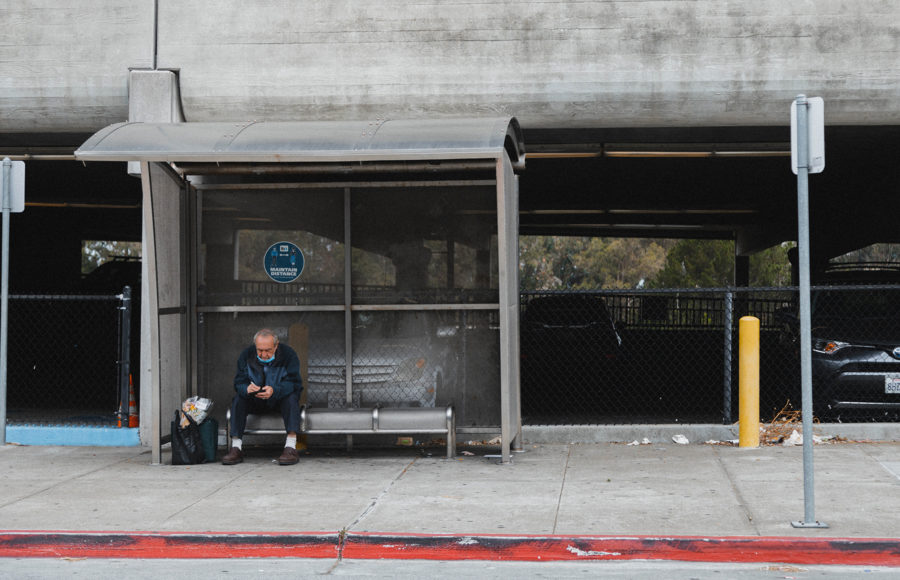 Photo of a man sitting on a bench at a bus stop