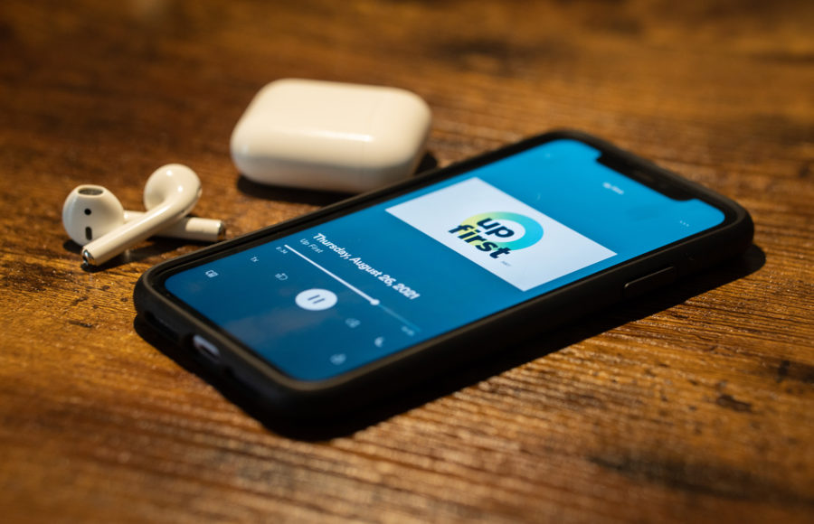 photo of a phone with the Up First podcast, and a pair of airpods
