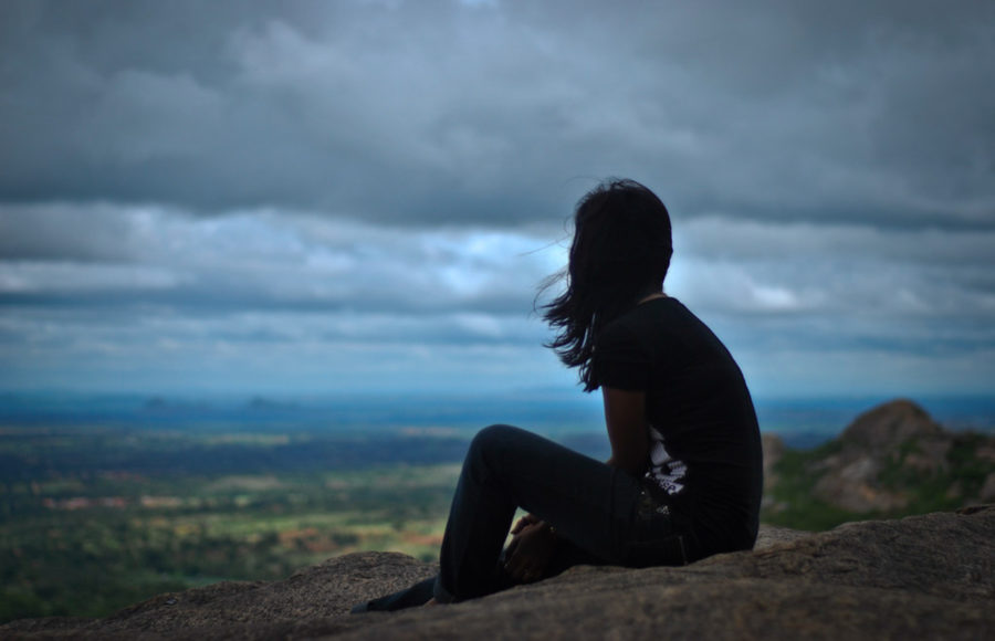 photo of a girl sitting alone overlooking a landscape
