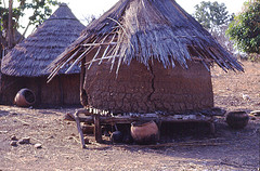 Abandoned Bedik storage structure in foreground, house in background, large ceramic brewing pots.  Southeast Sénégal (West Africa)