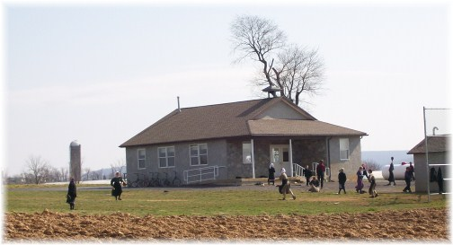 Amish children playing baseball at one room schoolhouse