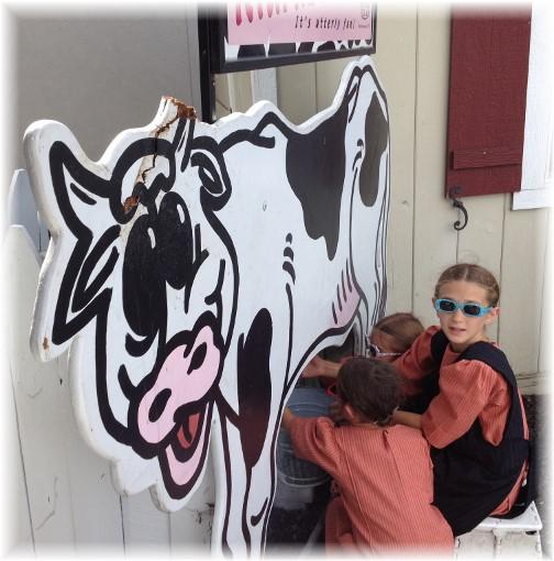 Amish children milking fake cow