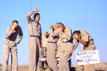 Men standing beneath an atomic bomb explosion