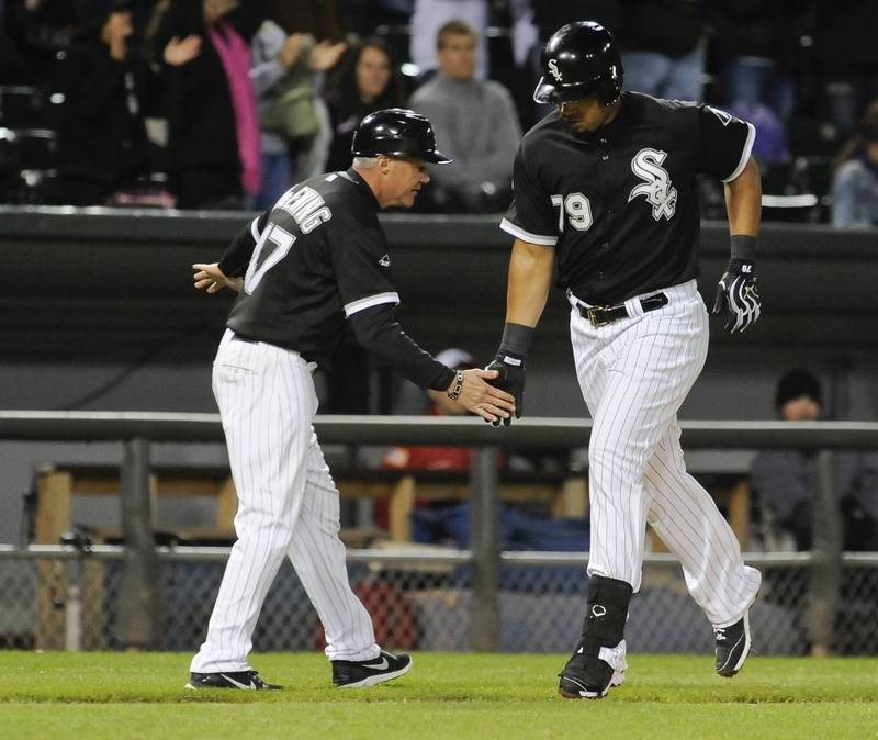 The White Sox's third-base coach Joe McEwing, left, celebrates with Jose Abreu after Abreu hit a solo home run against the Minnesota Twins during the second game of a baseball doubleheader Saturday at U.S. Cellular Field. Abreu also hit 100 RBIs for the season.