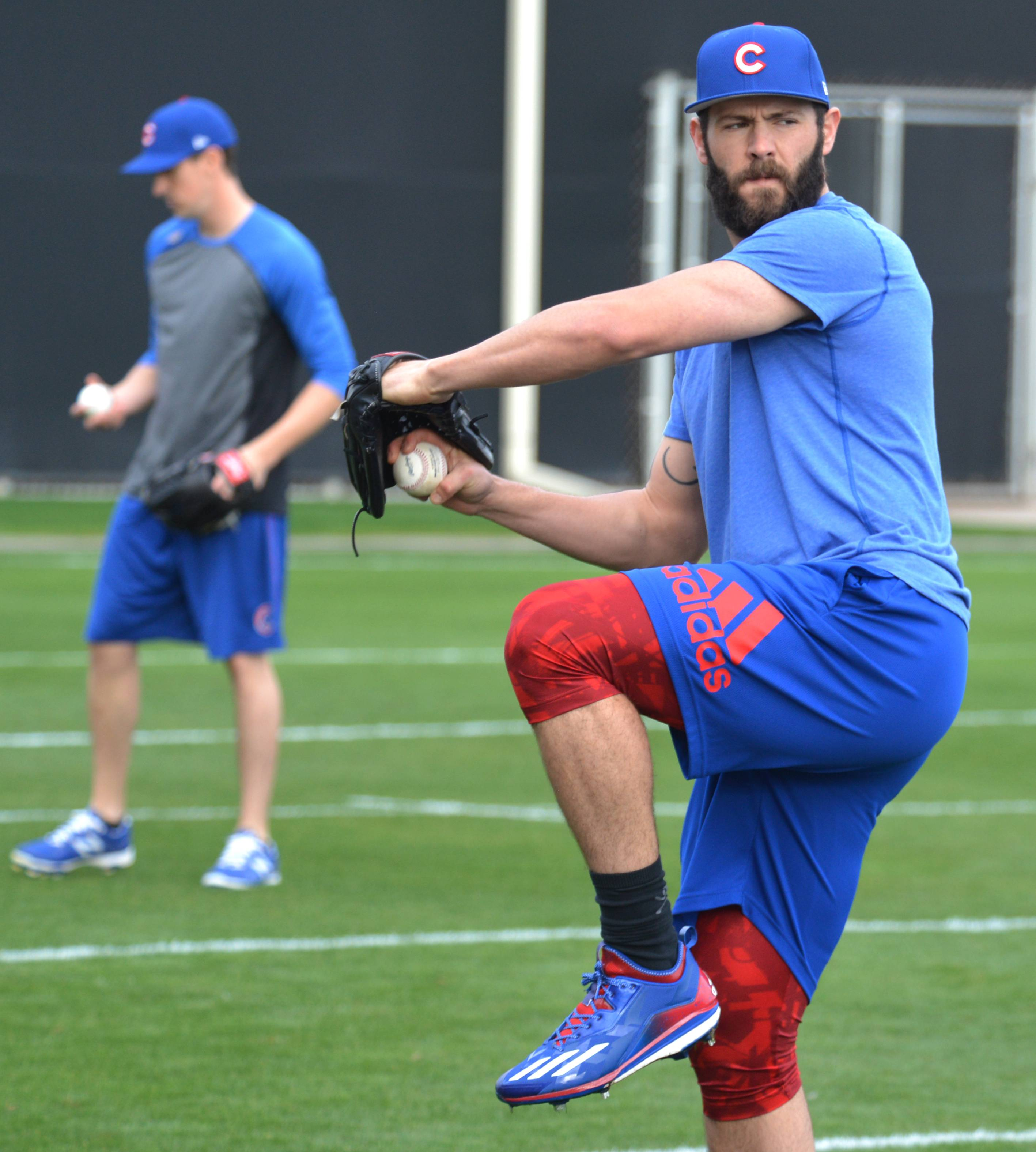Jake Arrieta got to work early as Cubs pitchers and catchers began report to training camp on Monday in Mesa, Ariz.