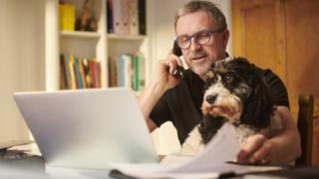 A man is on the phone, caressing his dog and at the same time examining assorted documents scattered on his open laptop