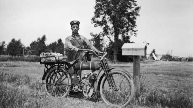 A rural postman stands with his Wagner 4-11 motorcycle next to a post office box on his route near Newell, South Dakota, circa 1915.