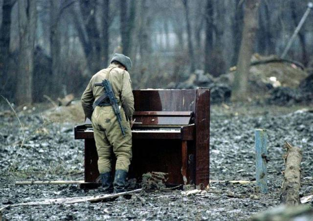 A Russian soldier playing an abandoned piano in Chechnya in 1994